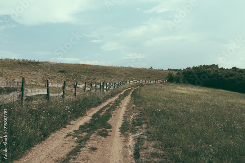 Empty country road with wooden fence