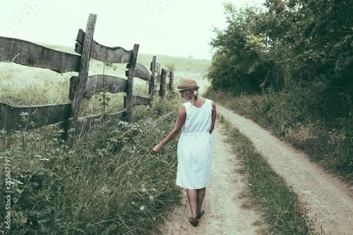 Woman walking alone on dirt road - 215867797