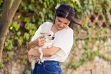 Latin girl with her lovely dog, a white chihuahua, outdoors. In a sunny day.