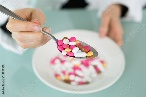 Foto Spatwand Apotheek colorful medicine capsule pill on spoon