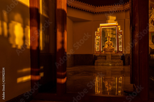 Foto Spatwand Boeddha Buddha statue in gold light pass through the window with reflection on the ground, Night shot photo.