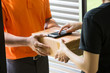 Woman hand accepting a delivery of boxes from deliveryman and signing on mobile phone - 215906337