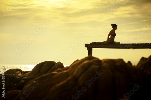 Plakat woman playing yoga pose on beach pier against beautiful sun rising sky