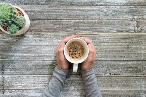 Wall mural Person holding a coffee mug on a wooden desk overhead view