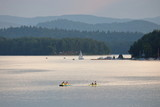 Jezioro Solińskie, Polska, lato, na wodzie jachty, rowerki wodne, kajaki, na drugim brzegu zielone wzgórza, tafla wody lśni srebrzyście