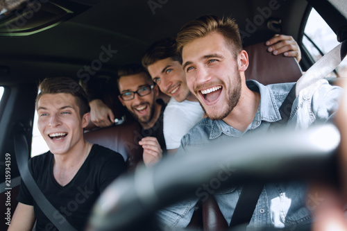 Group of happy friends on a car