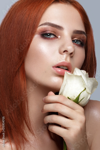 Foto Murales Beautiful red-haired girl with a classic make-up and rose in her hands. Beauty face. Photo taken in studio