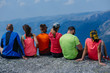 Leinwanddruck Bild - Back view of group six friends hikers relaxing together after intensive climbing. Team travelers sitting on peak stone and enjoying mountains view. Norway trip. Travel and adventures concept