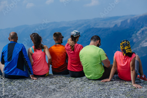 Leinwanddruck Bild Back view of group six friends hikers relaxing together after intensive climbing. Team travelers sitting on peak stone and enjoying mountains view. Norway trip. Travel and adventures concept