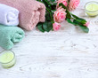 Quadro Candles, flowers and towels on white wooden background.