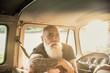 Portrait of a senior hipster inside their vintage van