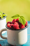 Ripe red raspberry in a emaned mug on old wooden table.