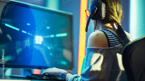 Shot of the Beautiful Pro Gamer Girl Playing in FPS Video Game on Her Personal Computer, Casual Cute Geek wearing Glasses and Headset. Neon Room. Playing Online Games.