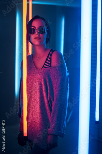 Portrait Shot of a Young Elegant Disco Girl Wearing Sunglasses. Room Lit in Retro / Retrowave Style with Neon and Pink Lights. - 215946713