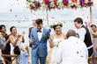 Leinwanddruck Bild - Cheerful newlyweds at beach wedding ceremnoy