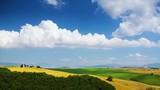 Clouds sky over Tuscany rolling hills; Italy countryside landscape with Tuscany farm land rolling hills