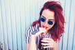 Preciosa chica pelirroja y tatuada tomando una bebida