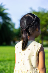 Back view of adorable little girl with beautiful hair walking in the park © domonite