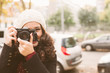 Leinwandbild Motiv Young beautiful woman with a woolen cap taking pictures with a retro camera in the city in autumn. Focus on camera