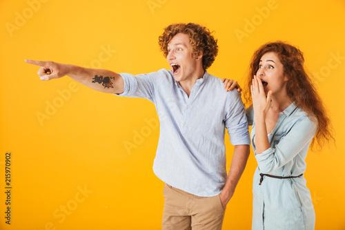Leinwandbild Motiv Excited friends loving couple pointing.