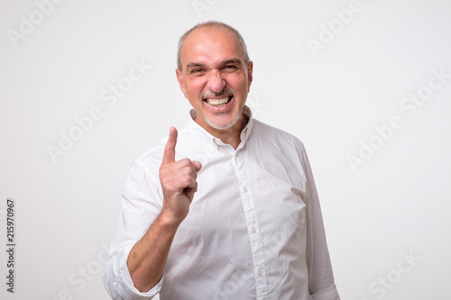 Satisfied mature hispanic man showing index fingers up, giving advice or recommendation