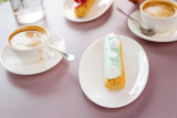 Sweet tooth. Close up of sweet eclair serving on plate which resting on pink surface - 215984302