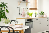 Real photo of sponge cake on a white, round dining table in open space kitchen interior with white cupboards - 215985562