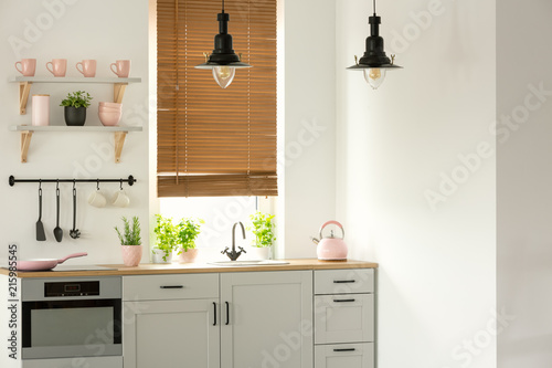 Foto Murales Real photo of a bright kitchen interior with wooden counter, black lamps, white cupboards and pink accents