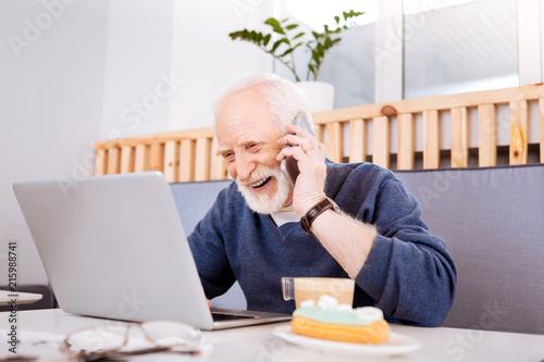 Foto Murales Fruitful cooperation. Joyful senior freelancer using laptop and communicating on phone