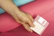 Bodegón minimalista colorido de disquete de color rosa sujetado por una mano sobre un fondo de colores rosa y azul