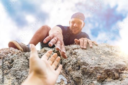 Leinwanddruck Bild Adventurers helping each other to climb
