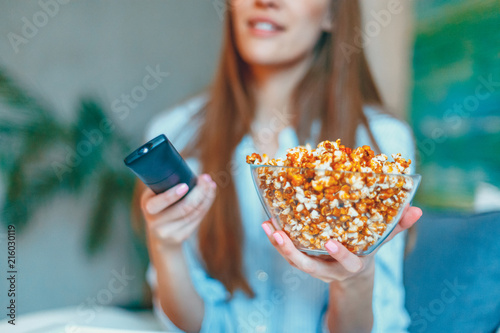 Beautiful young smiling woman watching a movie in the bed and eating popcorn.