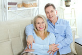 Middle aged couple relaxing on the couch smiling at camera at home in the living room - 216034515