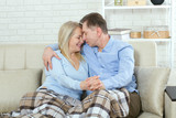 Middle aged couple relaxing on the couch smiling at camera at home in the living room - 216034542