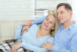 Middle aged couple relaxing on the couch smiling at camera at home in the living room - 216034755