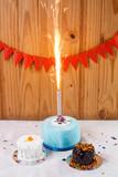Tortas de cumpleaños con bengala encendida y fondo con banderines rojos