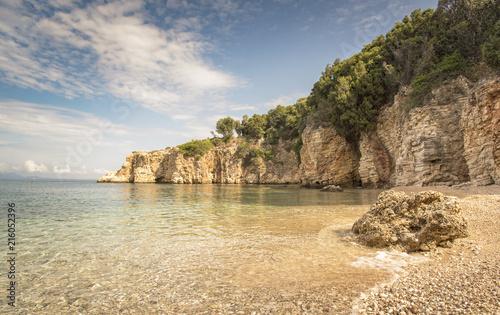 Fotobehang Beige Far reach of Dei beach in Syvota, Greece, rocky beach and clear Ionian sea