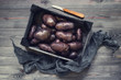 Fresh raw violet potatoes in the wooden tray
