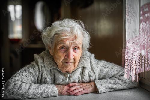 Leinwanddruck Bild Gray-haired elderly woman sitting near the window.