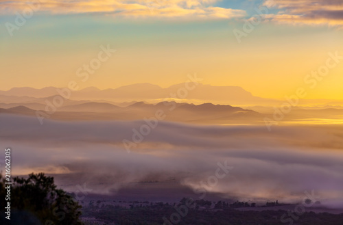 Foto Spatwand Oranje Mountain ridges protruding above low clouds at vivid sunset in Australia