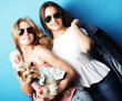 Quadro lifestyle and people concept: Two young girls friends standing together and holding dog