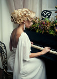 Beautiful young bride playing the piano - 216073781