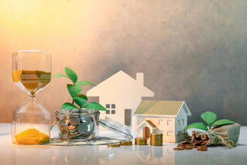 Real estate investment or property ladder. Home mortgage loan rate. Saving money concept. Plant growing out of coins in glass jar with dollar banknotes, hourglass, money bag and house model on table