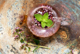 Herbal tea with mint and oregano in a glass teapot - 216081774