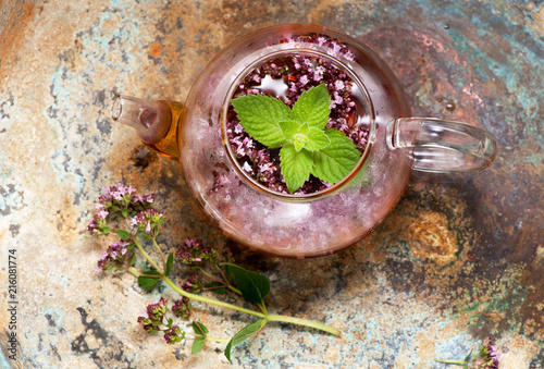 Leinwanddruck Bild Herbal tea with mint and oregano in a glass teapot