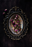 Retro still life with dried rose flowers on a metallic antique tray and bronze frame, top view