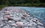 Large granite pebbles on the shore of a clean blue river in Norway