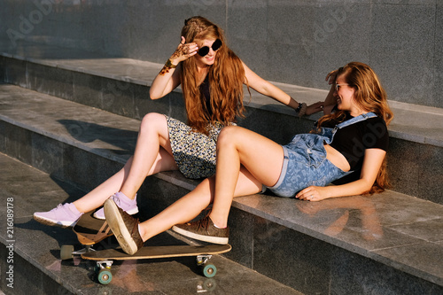 Foto Spatwand Skateboard Young beautiful redhead girls with longboard and skateboard posing outdoors in sunny day