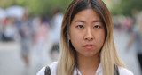 Young Asian woman in city serious face portrait - 216089776
