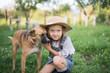 Leinwanddruck Bild - Girl and dog playing during autumn gardening in yard